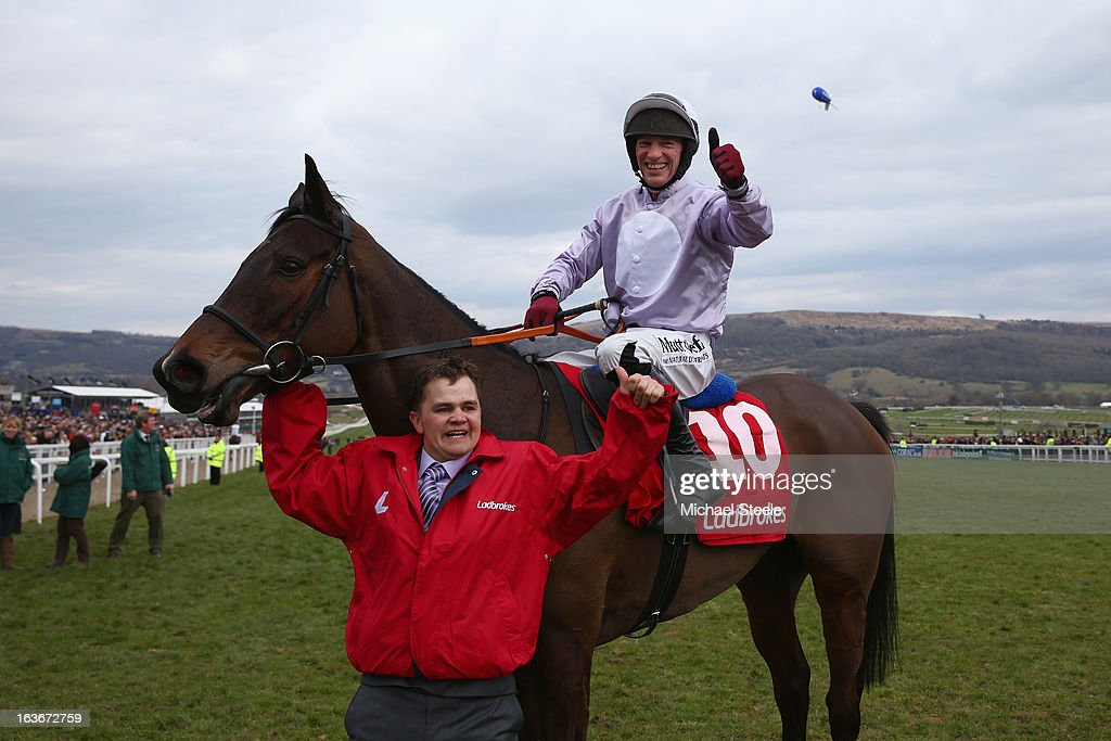 Paul Carberry onboard Solwhit celebrates winning the Ladbrokes World Hurdle race from Daryl Jacob (C) riding Celestial Halo on St Patrick's Thursday at Cheltenham Racecourse on March 14, 2013 in Cheltenham, England.