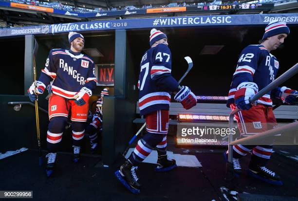 Paul Carey Steven Kampfer and Brendan Smith of the New York Rangers make their way to the ice for team warmup prior to the 2018 Bridgestone NHL...