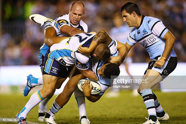 Paul Carter of the Titans tackles Sosaia Feki of the Sharks during the round one NRL match between the Cronulla Sharks and the Gold Coast Titans at...