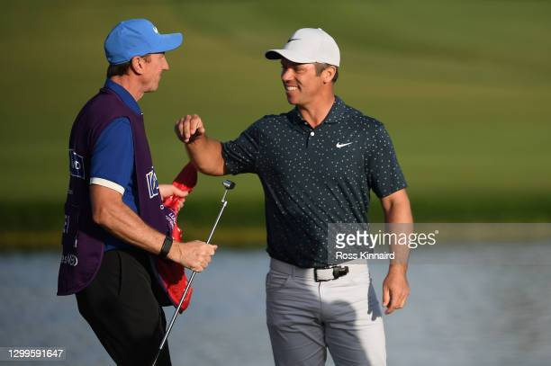 Paul Casey of England and his caddie John McLaren celebrate after claiming victory during the final round of the Omega Dubai Desert Classic at...