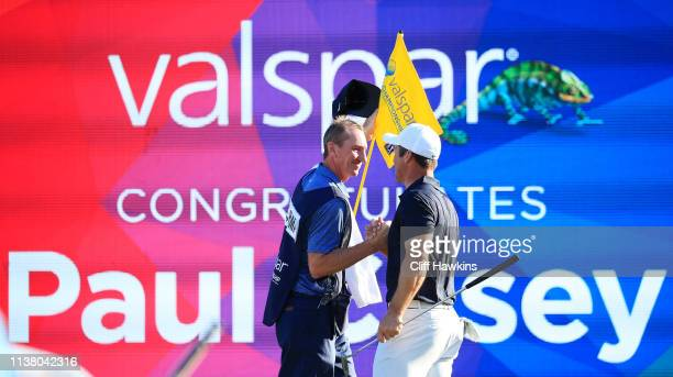 Paul Casey of England and his caddie John McLaren celebrate on the 18th green after winning the Valspar Championship on the Copperhead course at...