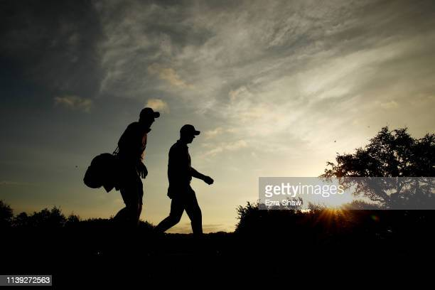 Paul Casey of England and his caddie John McLaren walk on the first hole in his match against Francesco Molinari of Italy during the fourth round of...