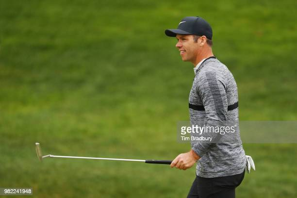 Paul Casey of England gestures to the gallery as he walks on the 18th hole during the third round of the Travelers Championship at TPC River...