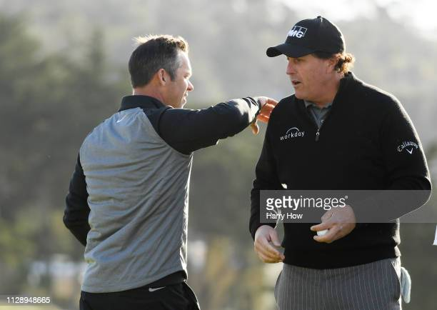 Paul Casey of England pats Phil Mickelson of the United States on the back on the 18th green during the continuation of the final round of the AT&T...