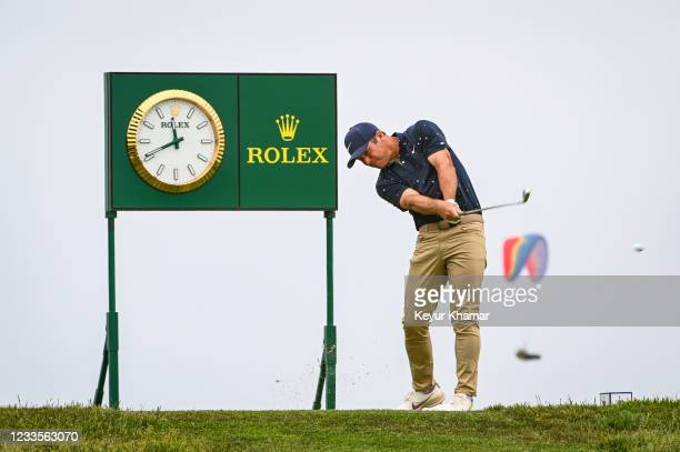 Paul Casey of England plays his shot from the 16th tee next to a Rolex clock as a paraglider flies by during the third round of the 121st U.S. Open...