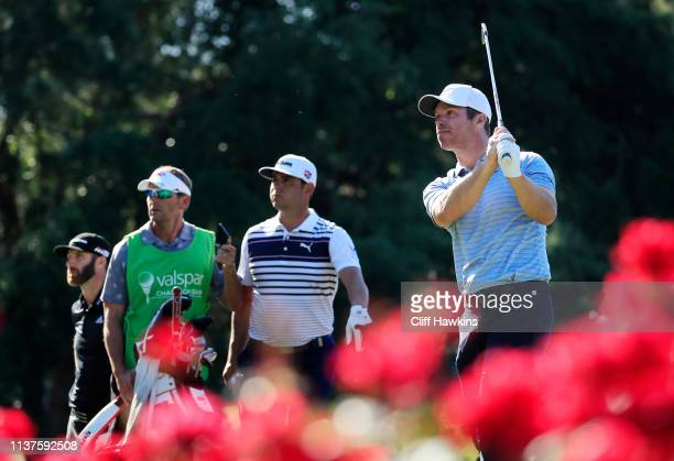 Paul Casey of England plays his shot from the 17th tee as Gary Woodland of the United States and Dustin Johnson of the United States look on during...