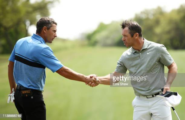 Paul Casey of England shakes hands with Charles Howell III of the United States on the 18th green after they halved their match during the second...