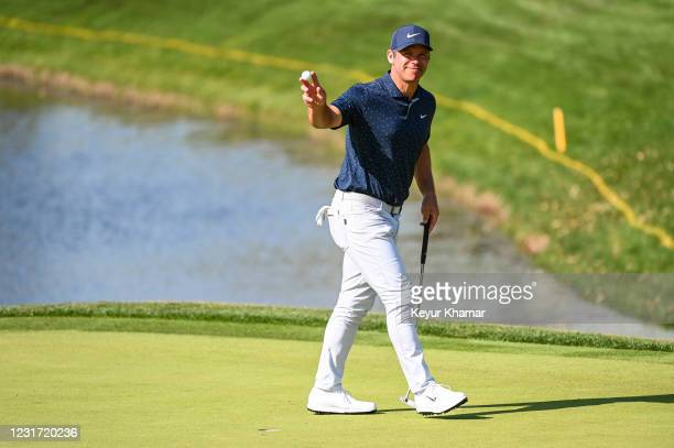Paul Casey of England smiles and waves his ball to fans after making a birdie putt on the 13th hole green during the final round of THE PLAYERS...