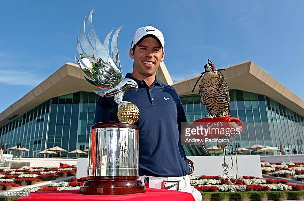 Paul Casey of England the defending champion poses for a photograph alongside the trophy with a falcon on his arm in front of the clubhouse during a...