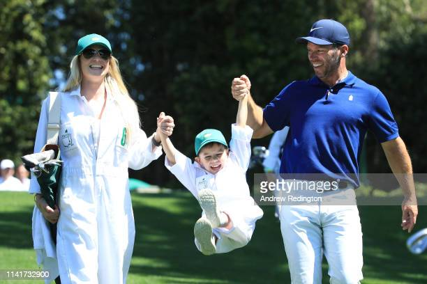 Paul Casey of England walks with wife Pollyanna and son Lex during the Par 3 Contest prior to the Masters at Augusta National Golf Club on April 10...