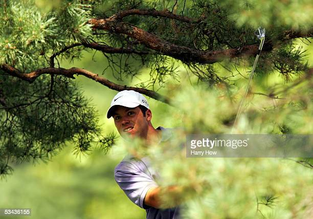 Paul Casey of England watches his tee shot from under a tree branch on the 11th hole during the first round of the WGC-NEC Invitational at the...