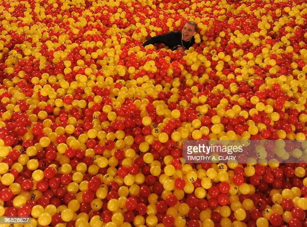 Paul Catzomo searches for a in a ball pit set up in Grand Central Station in New York on February 1 2010 to promote the largest lottery agreement in...