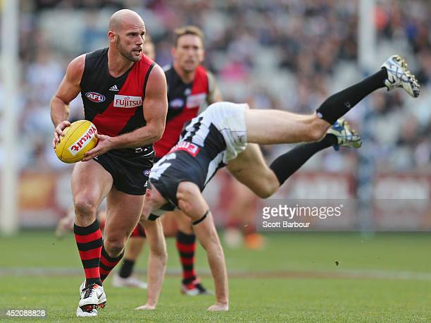 Paul Chapman of the Bombers beats the tackle of Nick Maxwell of the Magpies during the round 17 AFL match between the Essendon Bombers and the...