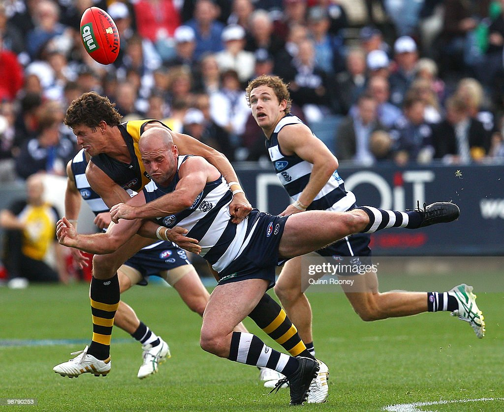 Paul Chapman of the Cats handballs whilst being tackle by Troy Simmonds of the Tigers during the round six AFL match between the Geelong Cats and the Richmond Tigers at Skilled Stadium on May 2, 2010 in Melbourne, Australia.