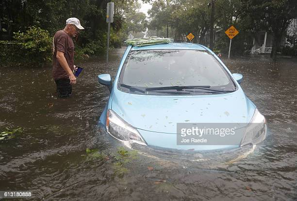 Paul checks on his car that sits in a flooded street as Hurricane Matthew passes through the area on October 7 2016 in St Augustine Florida Florida...