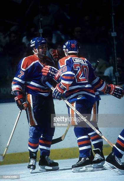 Paul Coffey and Billy Carroll of the Edmonton Oilers celebrate during an NHL game against the New York Islanders on March 29 1986 at the Nassau...