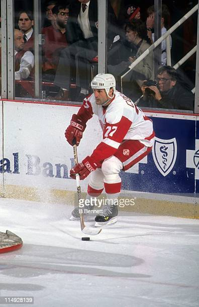 Paul Coffey of the Detroit Red Wings stops with the puck behind the net during an NHL game in February 1996 at the Joe Louis Arena in Detroit Michigan