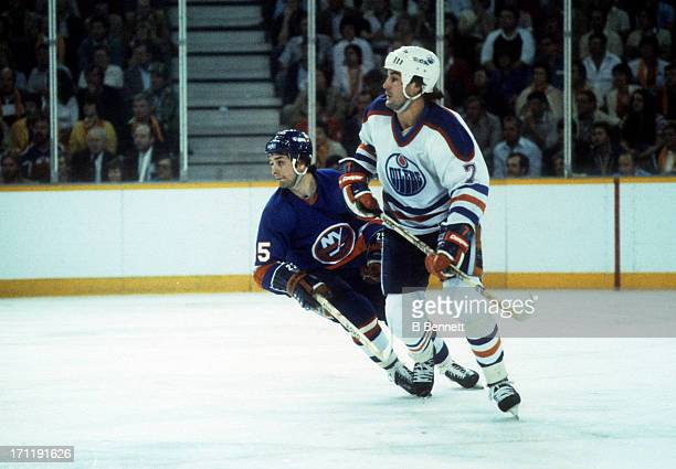 Paul Coffey of the Edmonton Oilers and Billy Carroll of the New York Islanders skate on the ice during the 1984 Stanley Cup Finals in May 1984 at the...