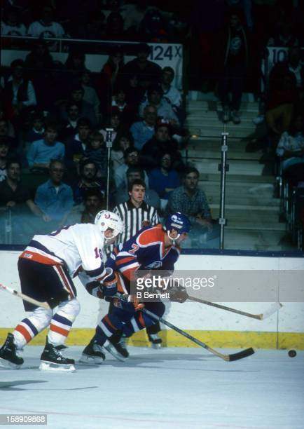 Paul Coffey of the Edmonton Oilers goes for the puck as he is pressured by Bryan Trottier of the New York Islanders on November 16 1985 at the Nassau...
