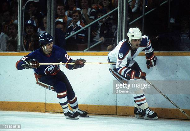 Paul Coffey of the Edmonton Oilers goes for the puck as he is hooked by Billy Carroll of the New York Islanders during the 1984 Stanley Cup Finals in...