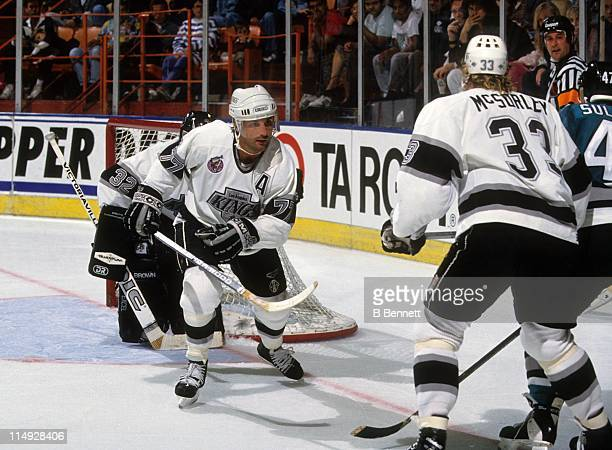 Paul Coffey of the Los Angeles Kings skates on the ice as his teammate Marty McSorley covers the player for the San Jose Sharks during their game...