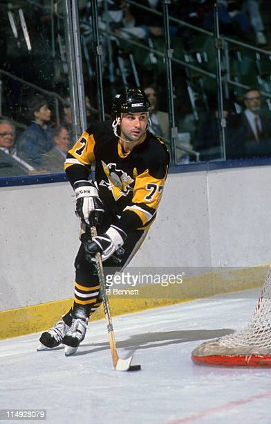 Paul Coffey of the Pittsburgh Penguins skates with the puck around the net during an NHL game circa 1990