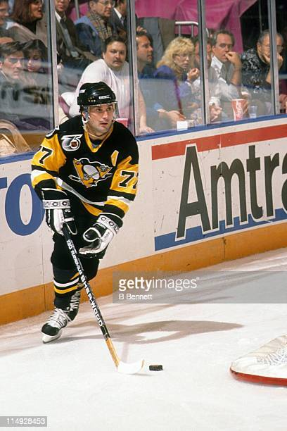 Paul Coffey of the Pittsburgh Penguins skates with the puck around the net during an NHL game in November 1991