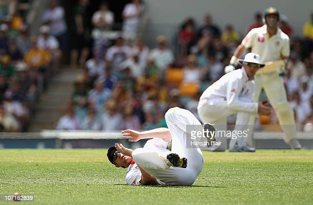 Paul Collingwood of England misfields the ball as Graeme Swann of England and Michael Hussey of Australia look on during day three of the First Ashes...
