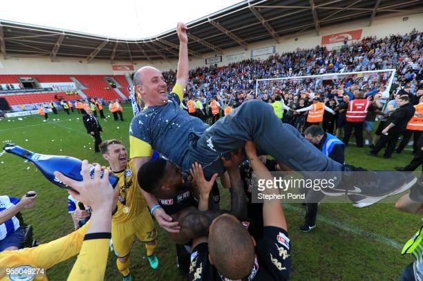 Paul Cook manager of Wigan Athletic is lofted in the air as they celebrate becoming League 1 Champions during the Sky Bet League One match between...