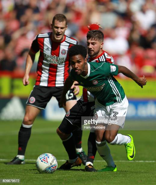 Paul Coutts of Sheffield United and Kieron Freeman of Sheffield United and Rico Henry of Brentford in action during the Sky Bet Championship match...