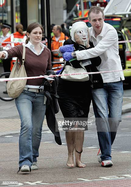 Paul Dadge and an unidentified person help Davinia Turrell to safety at Edgware Road underground station after several bomb blasts ripped across...