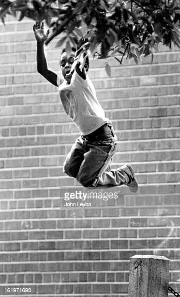 JUN 1 1987 Paul David LeShwwn Thomas Tye Jr of 1364 West 11th Ave goes air borne from a wooden stump pulling some leaves from a tree Been taking some...