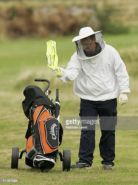 Paul Davies of a pest control service looks to clear the swarm of wasps away from the a golf bag during the Ryder Cup Wales 2010 Welsh National PGA...