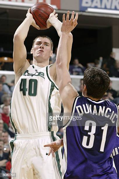 Paul Davis of Michigan State Spartans takes a shot as Davor Duvancic of the Northwestern Wildcats defends during the Big Ten Tournament March 12...