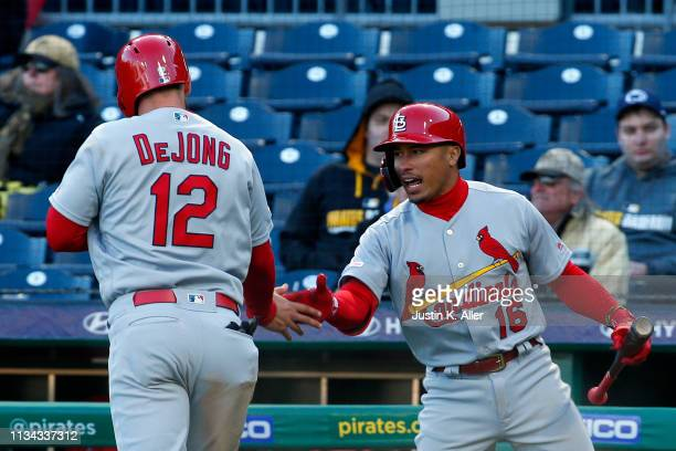 Paul DeJong celebrates with Kolten Wong of the St. Louis Cardinals after scoring on a past ball in the in the eleventh inning against the Pittsburgh...