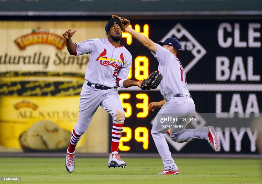 Paul DeJong #11 of the St. Louis Cardinals catches a fly ball as he collides with Dexter Fowler #25 in the ninth inning during a game against the Philadelphia Phillies at Citizens Bank Park on June 20, 2017 in Philadelphia, Pennsylvania. The Cardinals won 8-1 in 11 innings.