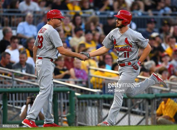 Paul DeJong of the St Louis Cardinals celebrates his home run with third base coach Mike Shildt during the third inning against the Pittsburgh...