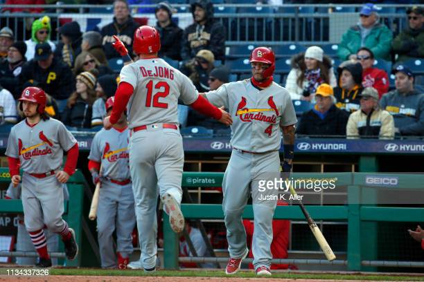 Paul DeJong of the St. Louis Cardinals celebrates with Yadier Molina of the St. Louis Cardinals after scoring on a RBI double in the ninth inning at...
