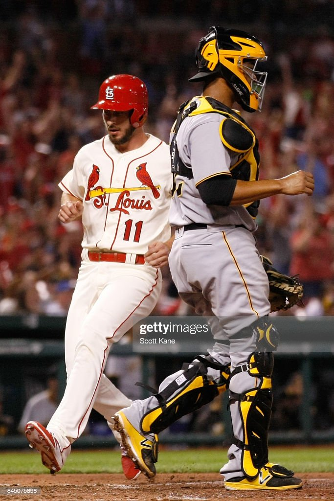 Paul DeJong #11 of the St. Louis Cardinals scores a run as Elias Diaz #32 of the Pittsburgh Pirates stands nearby during the eighth inning at Busch Stadium on September 9, 2017 in St. Louis, Missouri.