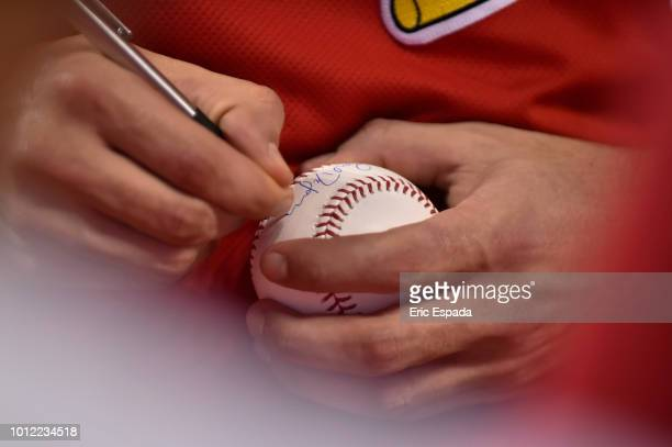 Paul DeJong of the St Louis Cardinals signs a baseball before the start of the game against the Miami Marlins at Marlins Park on August 6 2018 in...