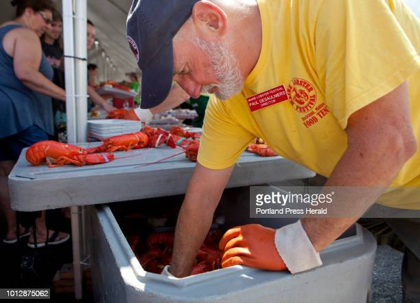 Paul DeSaulniers of Rockland unloads a fresh batch of lobster at the food tent during the Maine Lobster Festival in Rockland on Sunday August 5 2018...