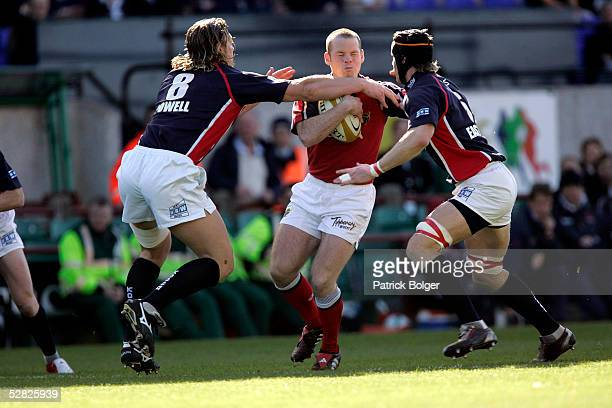 Paul Devlin of Munster is tackled by Andy Powell and Simon Easterby of Munster during the Celtic Cup Final between Munster and Llanelli Scarlets at...