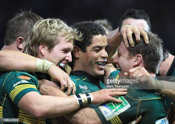 Paul Diggin of Northampton Saints celebrates his fourth try with team mates Joe Ansboro and Stuart Commins during the Heineken Cup match between...