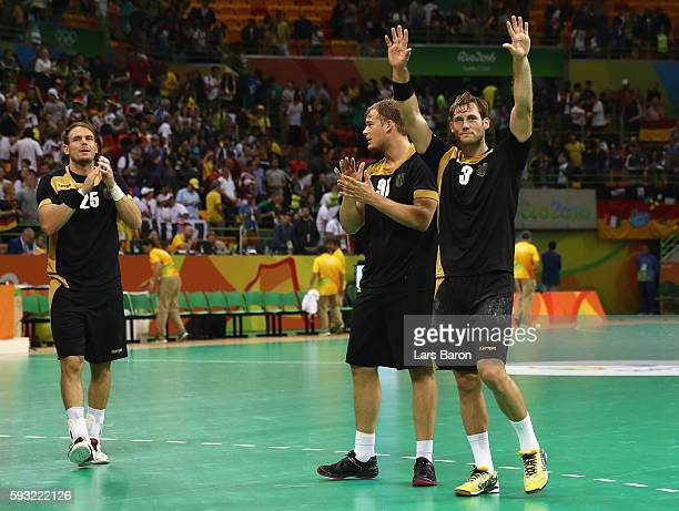 Paul Drux Kai Hafner and Uwe Gensheimer of Germany celebrate their victory following the Men's Bronze Medal Match between Poland and Germany on Day...