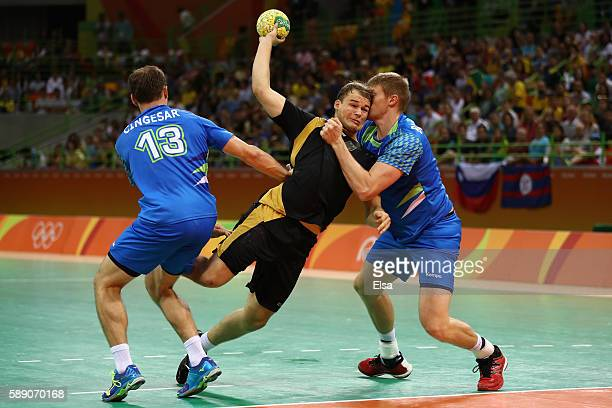 Paul Drux of Germany in action against Darko Cingesar and Blaz Blagotinsek of Slovenia during the Men's Handball preliminary Group B match between...