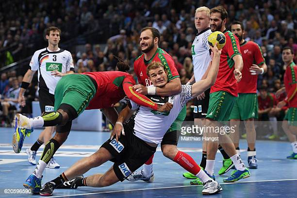 Paul Drux of Germany is challenged by Gilberto Duarte of Portugal and Daymaro Amador Salina of Portugal during the Handball European Championship...