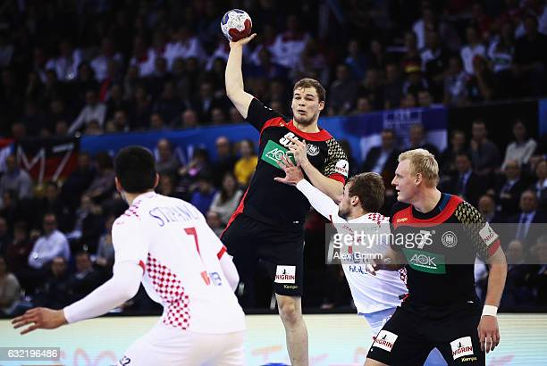 Paul Drux of Germany is challenged by Luka Cindric of Croatia during the 25th IHF Men's World Championship 2017 match between Germany and Croatia at...