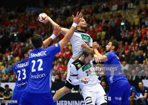 Paul Drux of Germany is challenged by Luka Karabatic and Ludovic Fabregas of France during the 26th IHF Men's World Championship 3rd place match...
