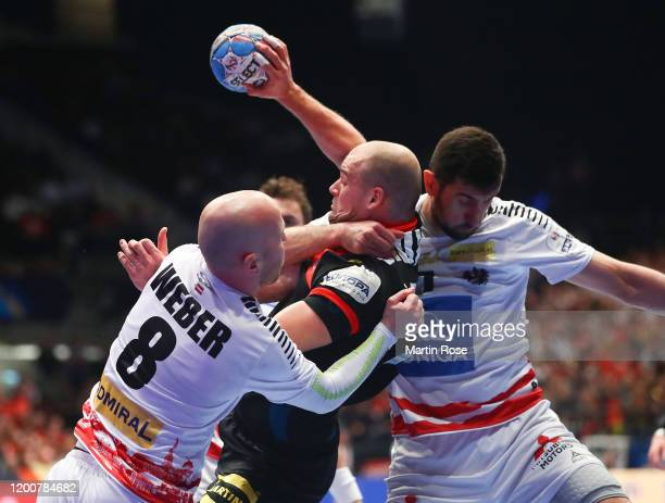Paul Drux of Germany is challenged by Robert Weber and Janko Božović of Austria during the Men's EHF EURO 2020 main round group I match between...