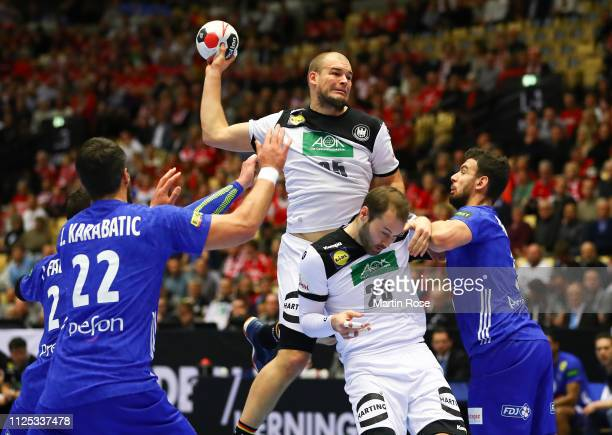 Paul Drux of Germany is challenged by several players of France during the 26th IHF Men's World Championship 3rd place match between Germany and...
